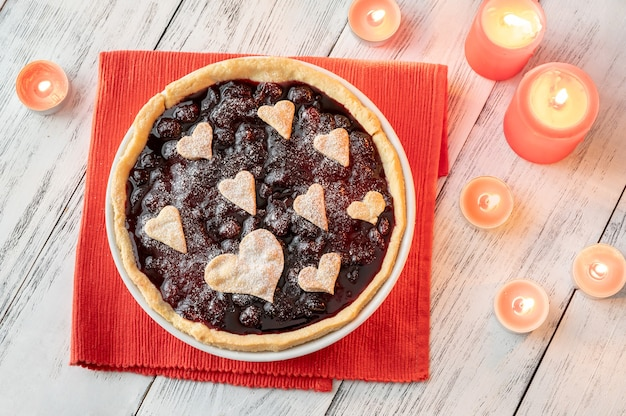 St. valentine's day cherry jam tart with burning candles
