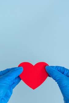 St. valentine's day during the coronavirus pandemic. two blue latex gloves hands hold a red heart shape on a blue background, close up, copy space, vertical frame