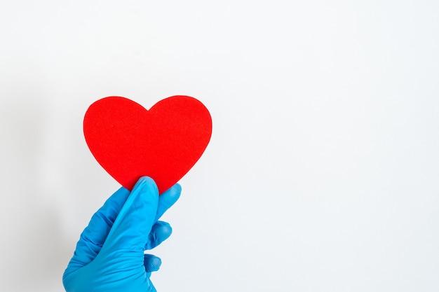 День святого валентина во время пандемии коронавируса. синяя латексная перчатка рука держит красную форму сердца на белом фоне, крупным планом, копией пространства