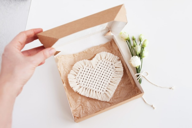 St. valentine's day gift with macrame decor. heart. natural materials, cotton thread. macrame eco decorations, ornaments, hand made decor in woman hand.