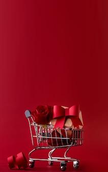 ギフトボックスが上昇した聖バレンタインのお祝いセールのコンセプトバナー、および赤に対してショッピングカート内の赤い紙のハート。