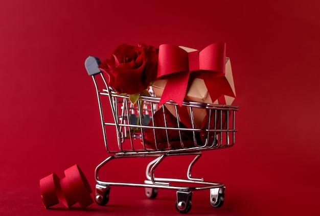St. valentine's festive sale concept banner with gift box rose, and red paper hearts in the shopping cart against a red.