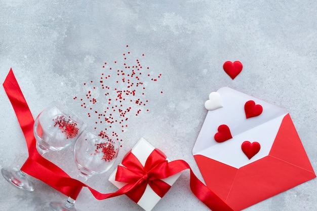 聖バレンタインデーの背景。布のハートが付いた赤い封筒、2つのつるの釉薬、赤いリボンと弓が付いた白いギフトボックス。
