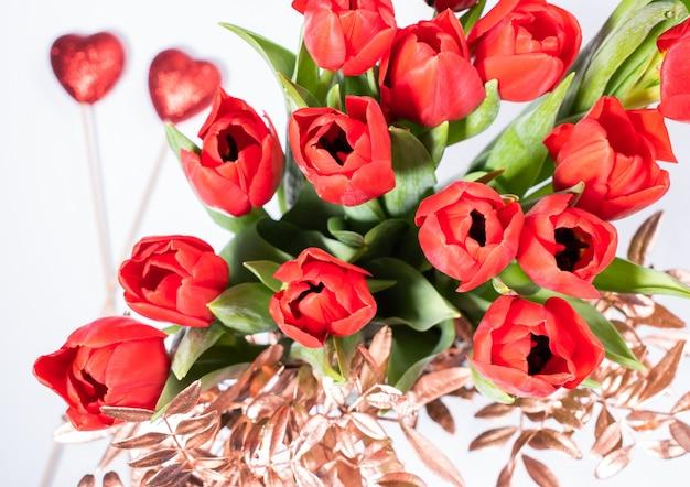 Композиция на день святого валентина с букетом тюльпанов и двумя красными сердечками на белом фоне