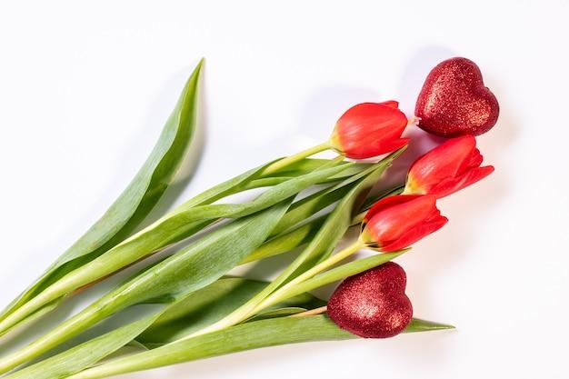 Композиция на день святого валентина с букетом тюльпанов и двумя красными сердечками на белой поверхности