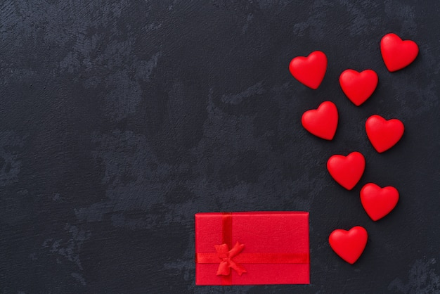 St. valentines day, red hearts and gift box on black background