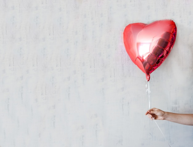 St vlentine banner with hand holding a red heart balloons on gray concrete wall copy space