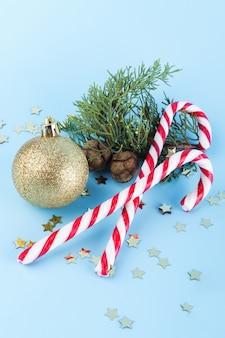 ゴールデンクリスマスボールとスプルースの枝でクリスマスキャンデー杖。背景、背景、壁紙、バナー、バナー、ペイント、背景、パターン、テキスタイル、カード、招待状、ご挨拶、はがき、アイコン、アイコン、ロゴ、エンブレム、ロゴタイプ、シンボル、記号、標識、スタンプ、ラベル、バッジ、st