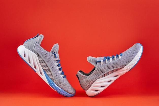 Стабильность и амортизация кроссовок. новые кроссовки или кроссовки других производителей на оранжевом фоне. обувь спортивная мужская. пара спортивной обуви.