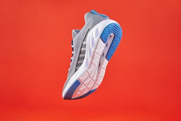 Стабильность и амортизация кроссовок. новые кроссовки или кроссовки других производителей на оранжевой стене. обувь спортивная мужская. пара спортивной обуви.