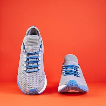 Stability and cushion running shoes. new unbranded running sneaker or trainer on orange wall. men's sport footwear. pair of sport shoes.