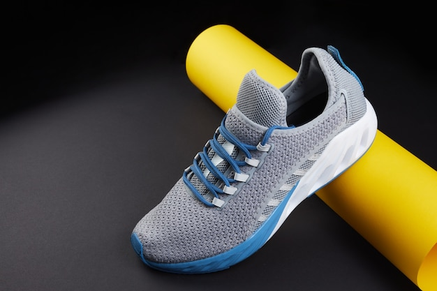 Stability and cushion running shoes. new unbranded running sneaker or trainer with yellow paper tube. men's sport footwear. pair of sport shoes.