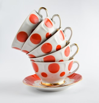 A stack of antique ceramic cups on a saucer