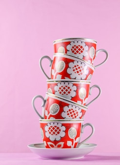 Stack of antique ceramic cups on wooden table against pink wall