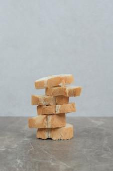 Pila di fette di baguette su marmo. foto di alta qualità