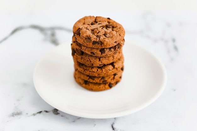 Stack of baked chocolate cookies on white plate over the marble background
