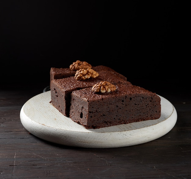 Stack of baked pieces of brownie chocolate cake with nuts on a wooden board, delicious dessert, close up