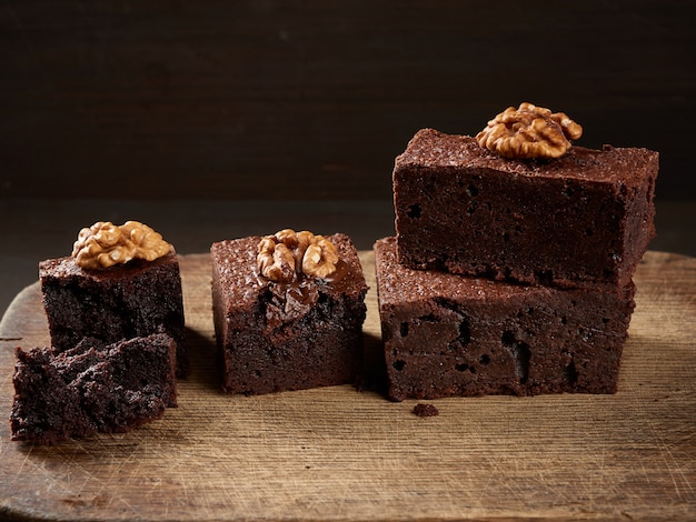 Stack of baked pieces of brownie chocolate cake with nuts on a wooden board