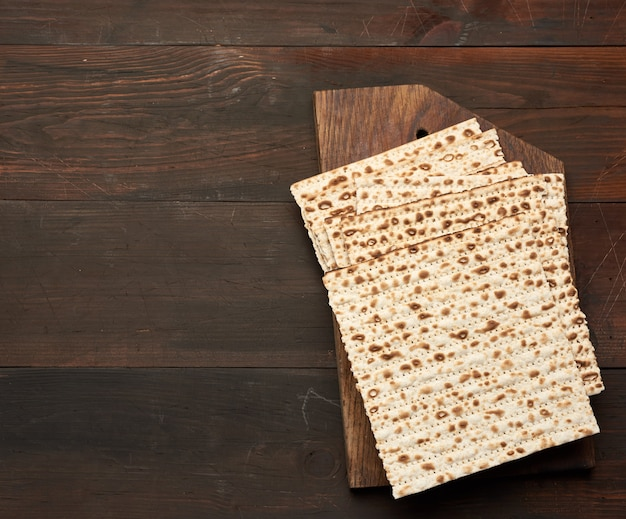 Stack of baked square matzo on a brown wooden space, top view