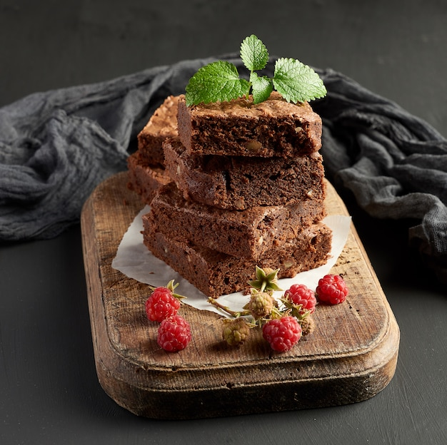 Stack of baked square pieces of chocolate brownie cake on brown wooden cutting board