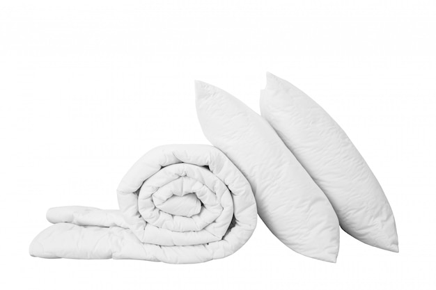 Stack of beddings on the white background, white pillow on the duvet isolated,