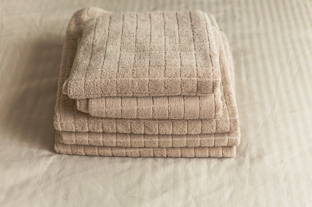 Stack of beige hotel towel on bed in bedroom interior. vintage toning