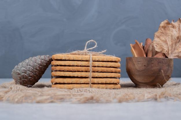 Pila di biscotti e bastoncini di cannella su tela da imballaggio. foto di alta qualità