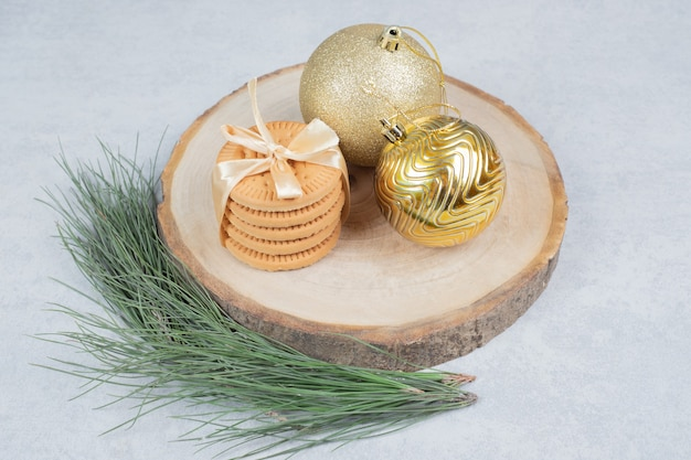 Stack of biscuits tied with ribbon and christmas balls on wooden board. high quality photo