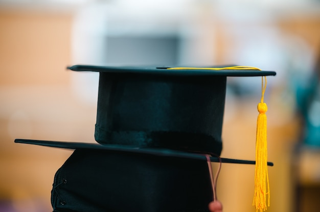 Stack a black graduation cap with a yellow tassel