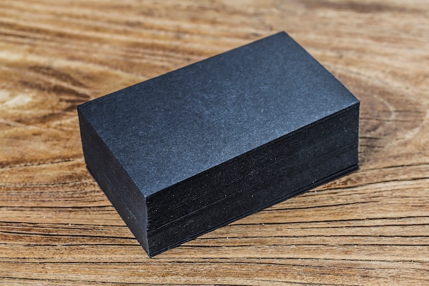 Stack of blank black business cards on wooden background