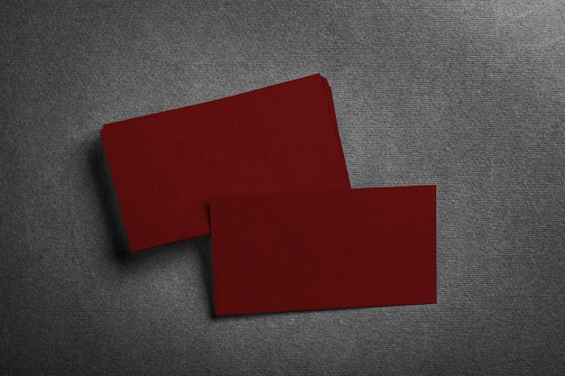 Stack of blank dark red business card on grey textured top view