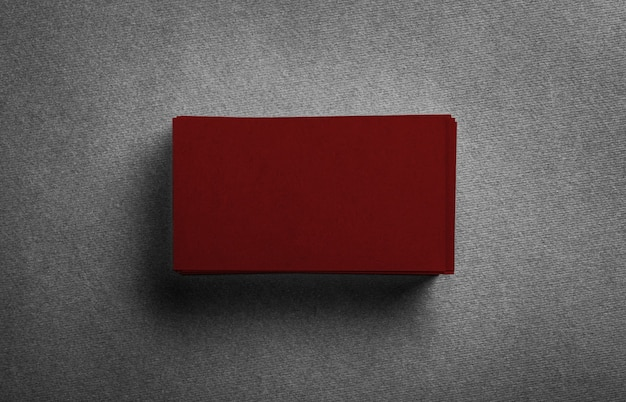 Stack of blank dark red business card on grey