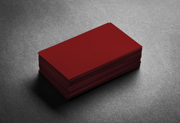 Stack of blank dark red business card on grey.