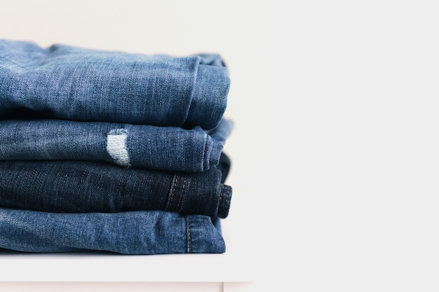 A stack of blue denim jeans or pants. textile industry concept. clothing stores concept. sale concept.