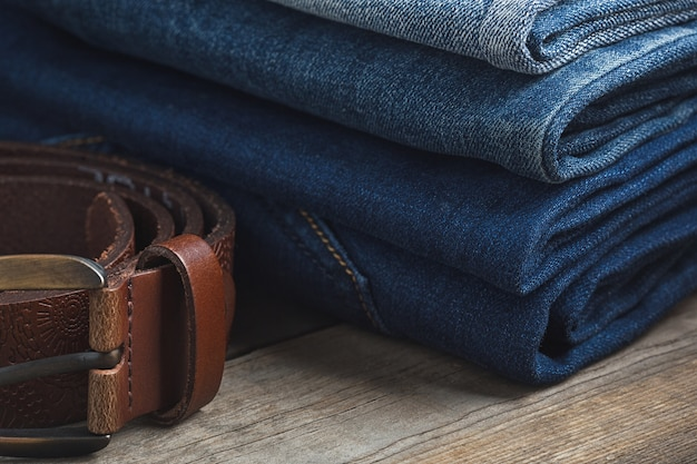 Stack of the blue jeans and brown genuine leather belt on wooden background