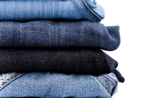 Stack of blue jeans closeup on white background