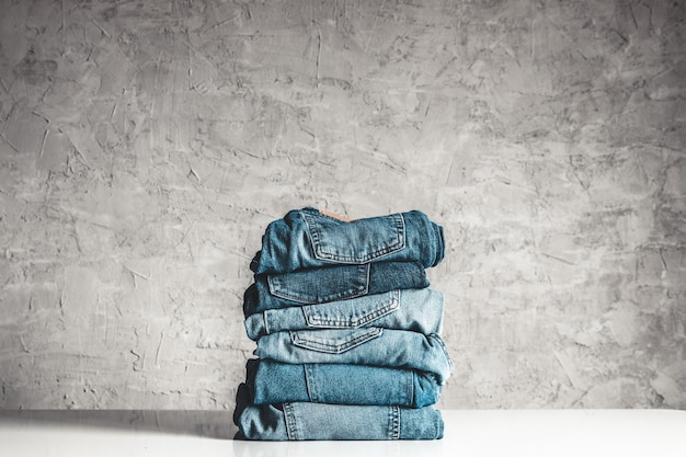 Stack of blue jeans on gray
