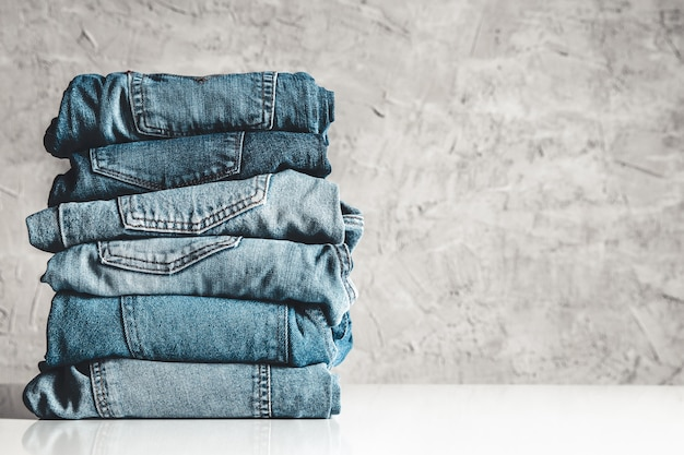 Stack of blue jeans on a gray