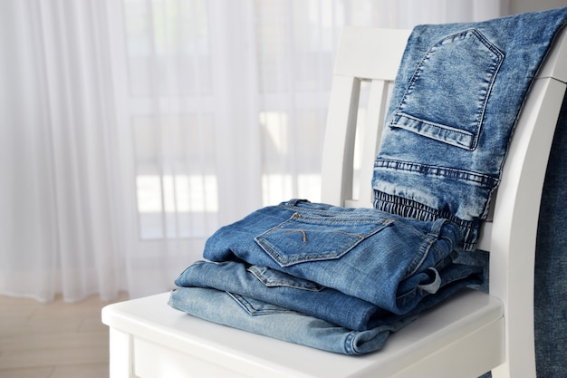 Stack of blue jeans trousers after laundry folded on white chair with tulle window