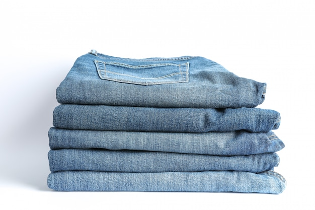 Stack of blue jeans on white background, space for text