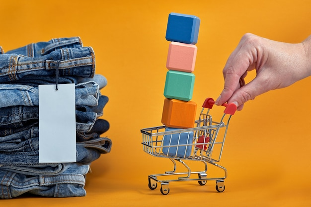A stack of blue jeans with a white blank tag on a yellow background