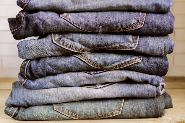Stack of blue jeans on wooden shelf. beauty and fashion clothing concept