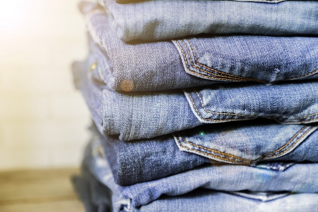 Stack of blue jeans on wooden shelf in sunlight. beauty and fashion clothing concept