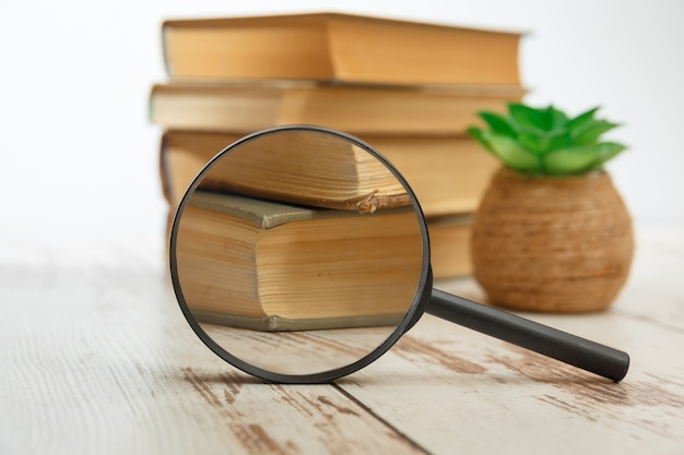 Stack book with magnifying glass, concept of search