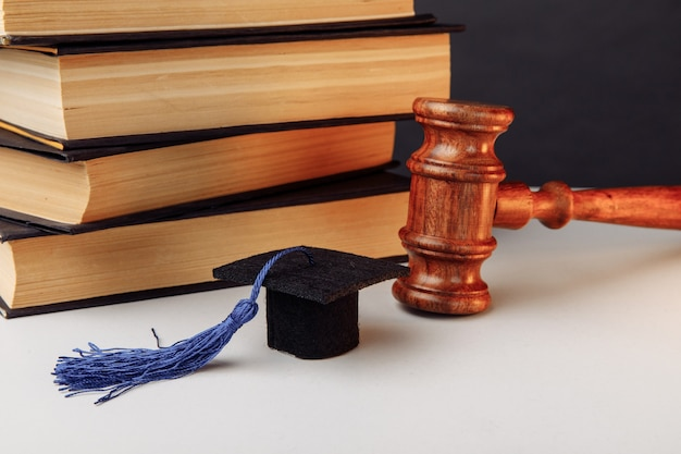 Stack of books, academic cap and wooden gavel.