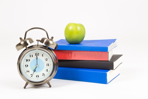 A stack books, alarm clock and apple on desk, isolated on white