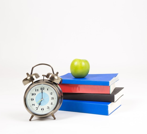 A stack books, alarm clock and apple on desk