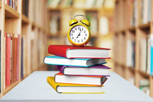 Stack of books and alarm clock isolated on background