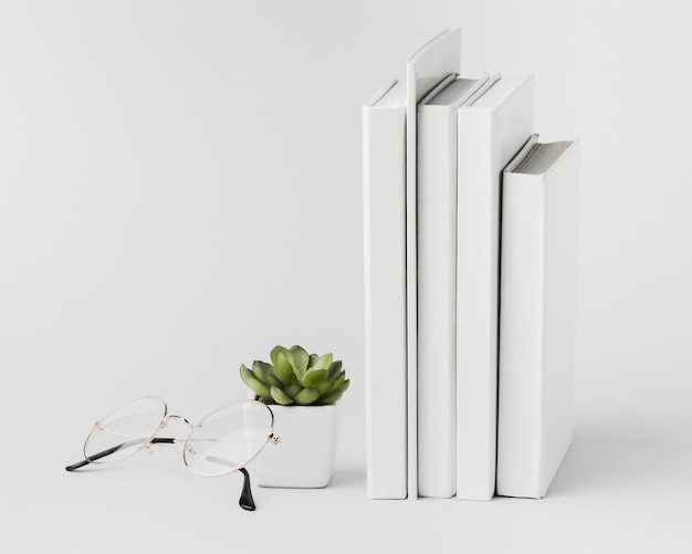 Stack of books aligned with plant