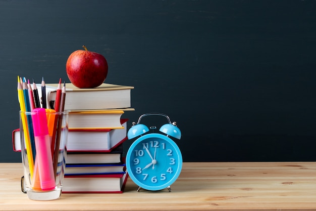 Stack of books, apple, alarm clock and pencils on wooden table over chalkboard background